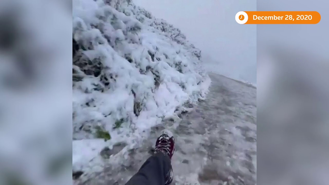Tobogganist enjoys snowy conditions on hillside path