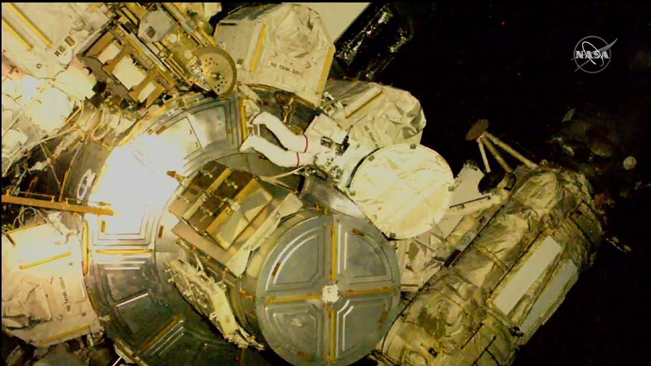 Spacewalking astronauts work on ISS plumbing